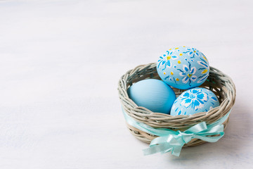 Easter pale blue painted eggs in the wicker basket