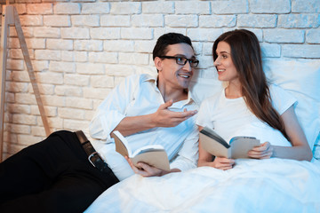 Young businessman reads book in bed with his white woman. Man and woman lying in bed at home.