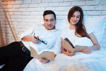 Young businessman reads book in bed with his wife. They are lying in bed at home.