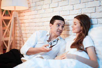 Young businessman reads book in bed with white woman. Young couple couch are discussing business.