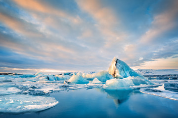 Icebergs float on Jokulsarlon glacier lagoon at sunrise, in Iceland.