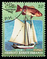 Schooner and fish on postage stamp