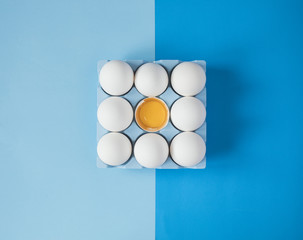 White raw chicken eggs on colorful blue background