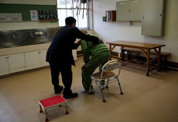 A prison officer helps an elderly inmate during the inmate's mobility function checking in a special building set aside for elderly unable to do regular prison factory work, at the Tokushima prison in Tokushima