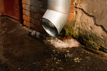 A drain pipe with a piece of melting ice in the spring on the street