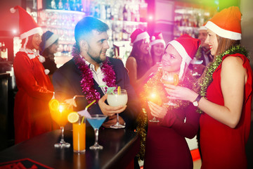 Man and two women in Santa hats celebrating at nightclub