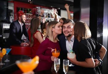 Two women kissing man at nightclub