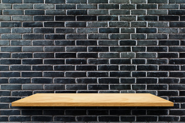 Empty wood board shelf at black brick wall background,Mock up for display or montage of product or...