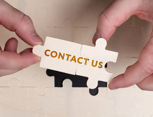 The concept of business, technology, the Internet and the network. A young businessman collects a puzzle with the proper inscription: Contact us