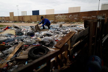 Alexis, 22, laborer, collects plastic near prototypes of President Donald Trump's border wall with Mexico, behind the current border fence in this picture taken from the Mexican side of the border in Tijuana