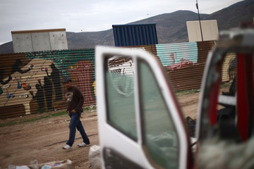 A man walk passes near prototypes of President Donald Trump's border wall with Mexico, behind the current border fence in this picture taken from the Mexican side of the border in Tijuana