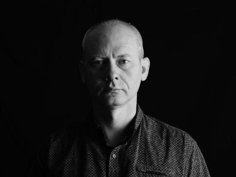 Portrait of serious man on dark background.