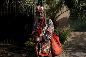 A Sufi man wears traditional colorful quilted cap and attire as he stands outside a building in Karachi,
