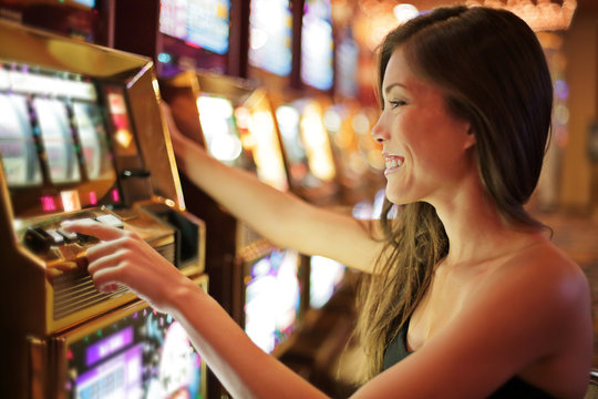 Asian woman gambling in casino playing on slot machines spending money. Gambler addict to spin machine. Asian girl player, nightlife lifestyle. Las Vegas, USA.