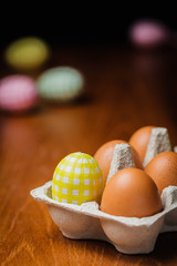 Decorated yellow and brown hen eggs in cardboard box
