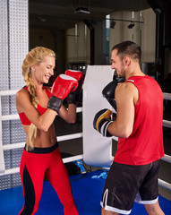 Boxing workout woman in fitness class ring. Man trainer holding sport mitts in gym. Sport female box gloves are red backview. Love couple trains together.