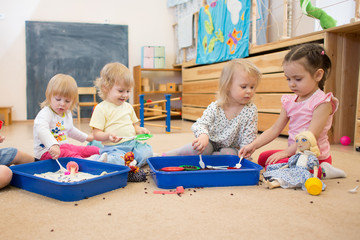 Obraz Group of children playing in kindergarten or daycare centre - fototapety do salonu