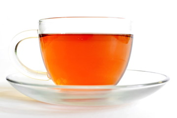 hot black tea in transparent glass cup on saucer on white background