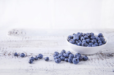 Berries in a bowl / Blueberry in a white bowl on a wooden white table
