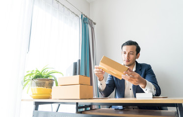 Thoughtful business man is looking at his packaging delivery boxes