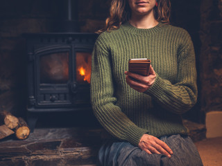 Young woman using smart phone by the fire