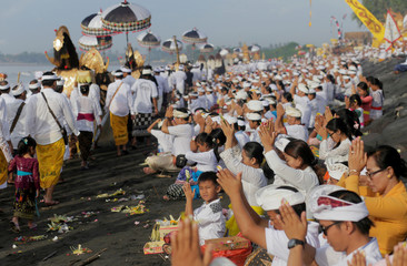 Balinese Hindu pray along a beach during a Melasti  purification ceremony ahead of the holy day of Nyepi in Gianyar, Bali