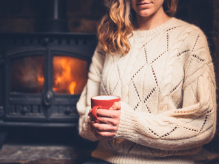Woman in white jumper by fireplace with mug