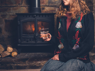 Woman in christmas jumper with drink by fire