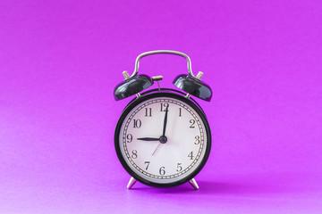 Black modern alarm clock set at nine o'clock, isolated, work school begins concept, ultraviolet background