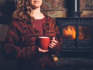 Woman in red jumper with mug by fire