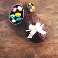 Chocolate Easter eggs on wooden background with ribbon bow and candies.