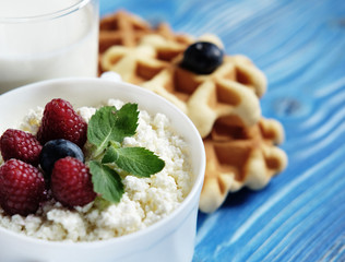 Cottage cheese with berries, waffles and milk on a wooden blue b