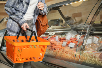 Young woman with shopping basket choosing sausage products in supermarket