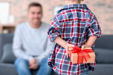 Cute little boy holding gift for father behind his back, closeup