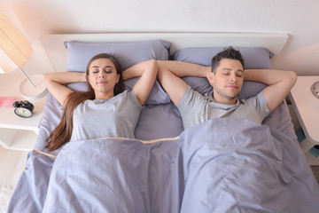 Young couple sleeping in bed at home. Family bedtime
