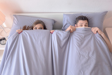 Young couple hiding under blanket on bed at home