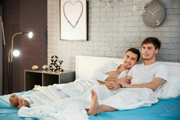 Young gay couple lying in bed at home