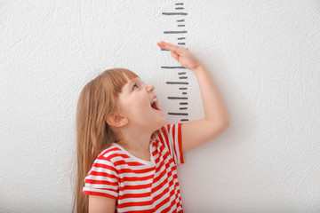 Cute little girl measuring height on light background