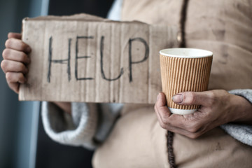 Poor woman holding piece of cardboard with word HELP and cup, closeup