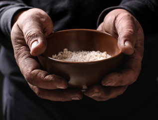 Poor man holding bowl with rice, closeup