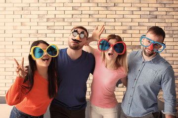 Young people in funny disguise posing on brick wall background. April fool's day celebration