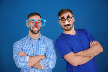 Young men in funny disguise posing on color background. April fool's day celebration