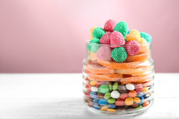 Jar with tasty candies on table against color background