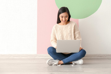 Young Asian woman using laptop on floor indoors