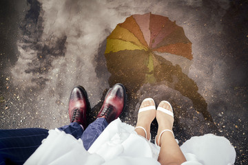 The bride and groom standing in the puddle, colorfull umbrella visible in the reflection.