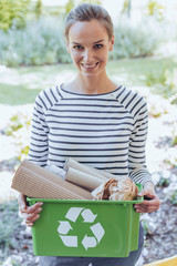 Smiling woman holding green bin
