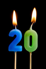 Burning candles in the form of twenty figures (numbers, dates) for cake isolated on black background. The concept of celebrating a birthday, anniversary, important date, holiday, table setting
