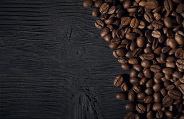 coffee beans on a black old  wooden bg top view