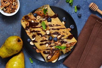 Homemade thin pancakes with caramelized pears, chocolate sauce and nuts on a concrete background.