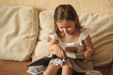 little girl looks at a family album
